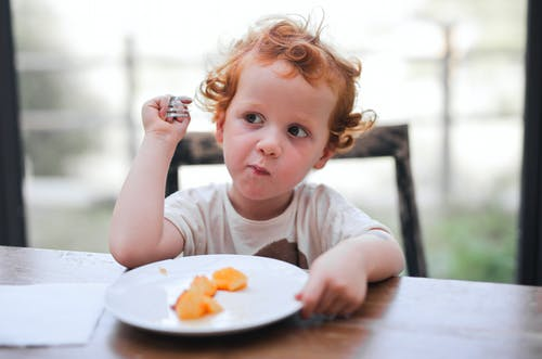 Child in White Crew Neck T-shirt Eating on Brown Wooden Table