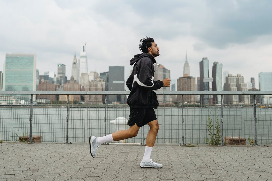 Man in Black and White Jacket and Black Shorts Running on Track Field