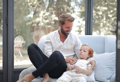 Man in White Dress Shirt and Black Pants Sitting Beside Baby in White Onesie