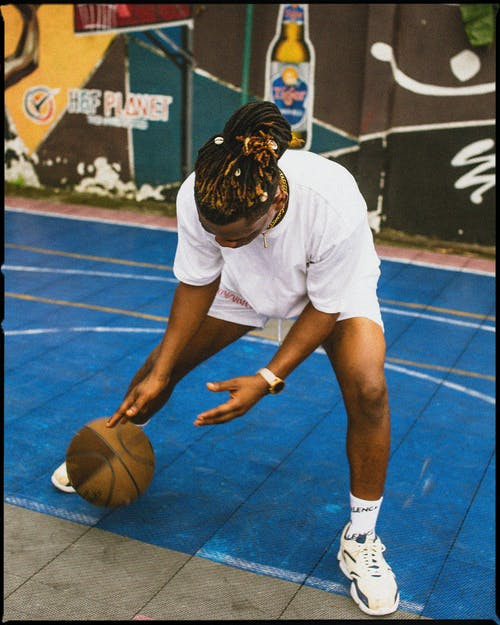 Full body sporty African American male in white sportswear dribbling basketball ball while playing basketball on street court