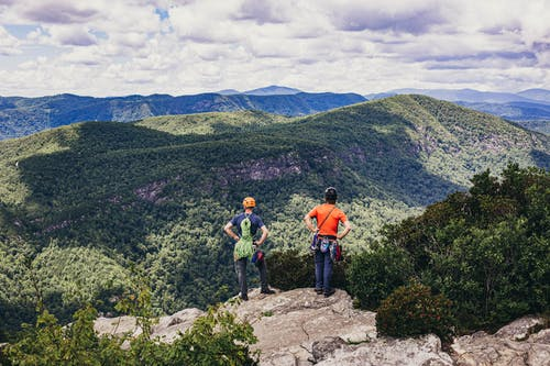 Man and Woman Standing on Rock Mountain