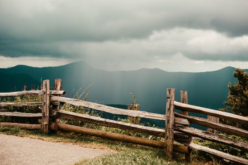 Brown Wooden Fence on Brown Field Under Gray Clouds