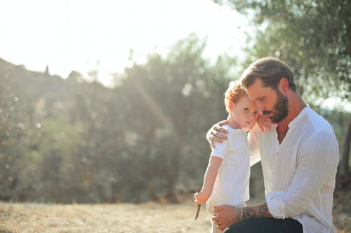 Woman in White Long Sleeve Shirt and Blue Denim Jeans Holding Girl in White Long Sleeve