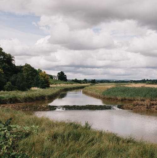 Narrow river between grass fields under sky in countryside