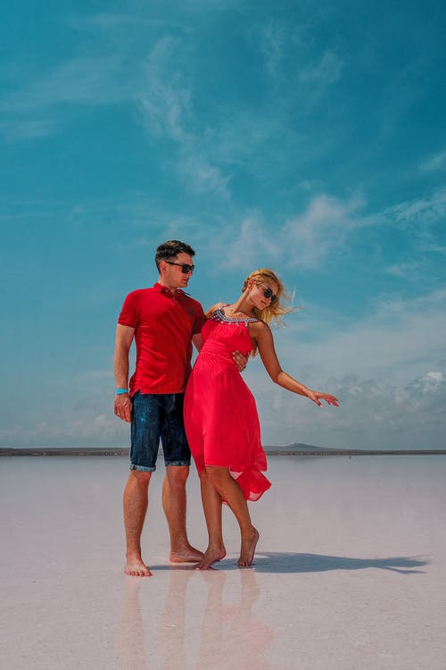 Romantic young couple enjoying summer day on sandy beach