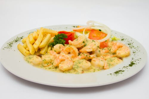 Shrimps With French Fries and Vegetables on White Ceramic Plate