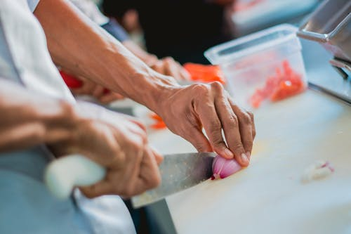 Person Chopping Onion with Kitchen Knife