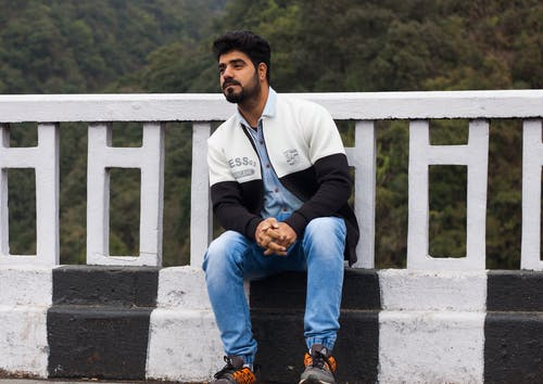 Man in Jacket and Blue Denim Jeans Sitting by the Roadside