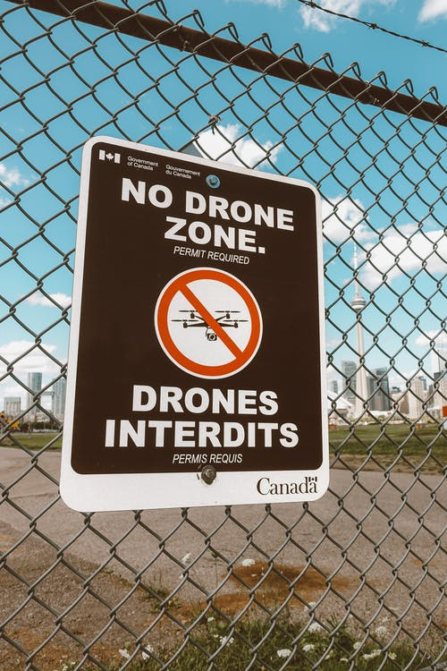Metal fence with barbed wire in front of city with sign prohibiting to use drones