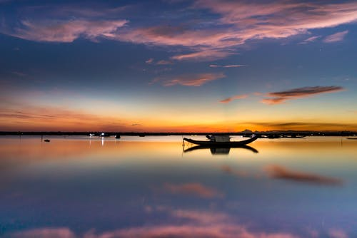 Scenic sunset over calm lake with boats