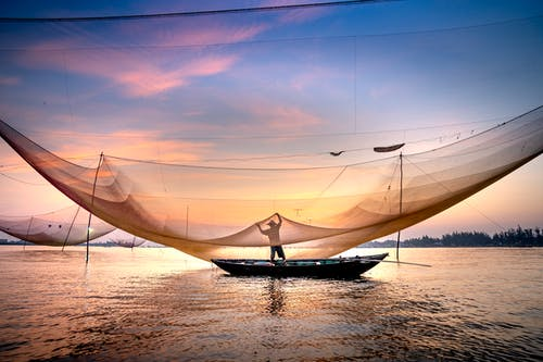 Silhouette of fisher standing in boat on rippling surface of lake and lifting up fishing net over water at sunset