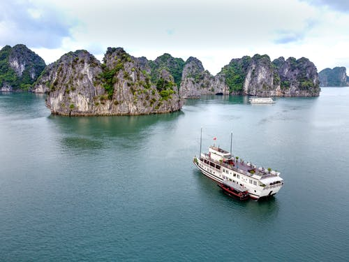 Height view of cruise vessel sailing in calm ocean to big rocks overgrown with green plants in daylight