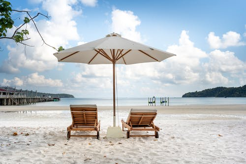 Loungers and parasol on seashore