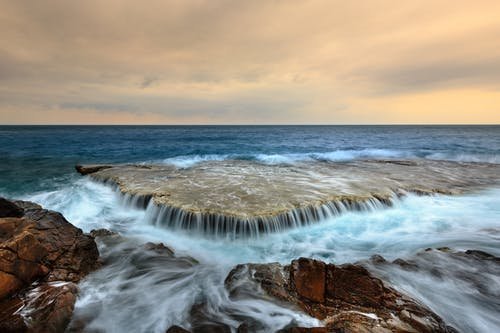 Picturesque scenery of endless ocean with foamy waves washing rocky coast against cloudy sunset sky