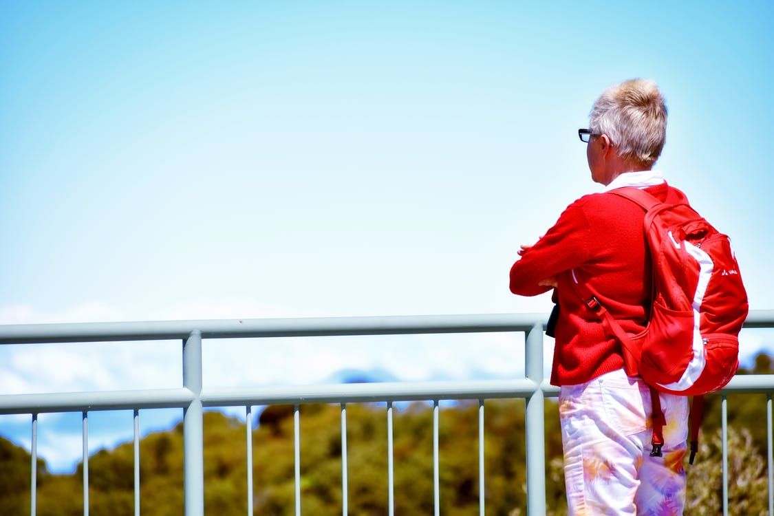 Woman in Red Long Sleeve Shirt Standing Near White Railings Looking at the View