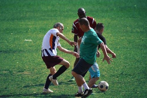 Men Playing Soccer on Green Grass Field