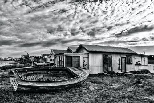 Grayscale Photo of Wooden Boat on Shore near Houses