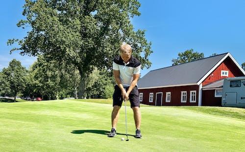 Man Wearing a Polo Shirt and Shorts Playing Golf