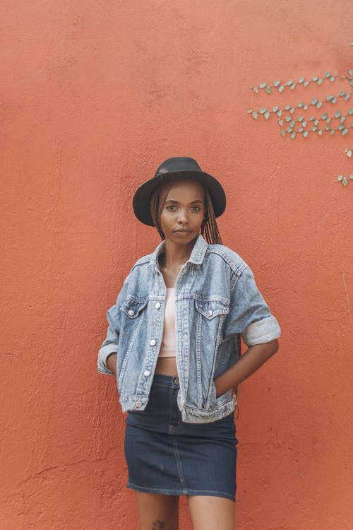 Woman Wearing a Denim Jacket and Skirt Standing on a Wall