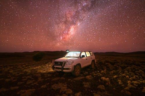White Suv on Brown Field Under Starry Night