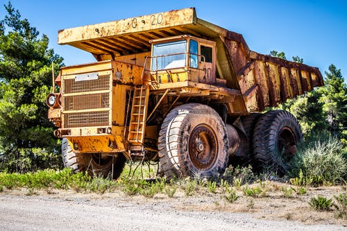 Weathered dump truck on sandy road near green trees in countryside