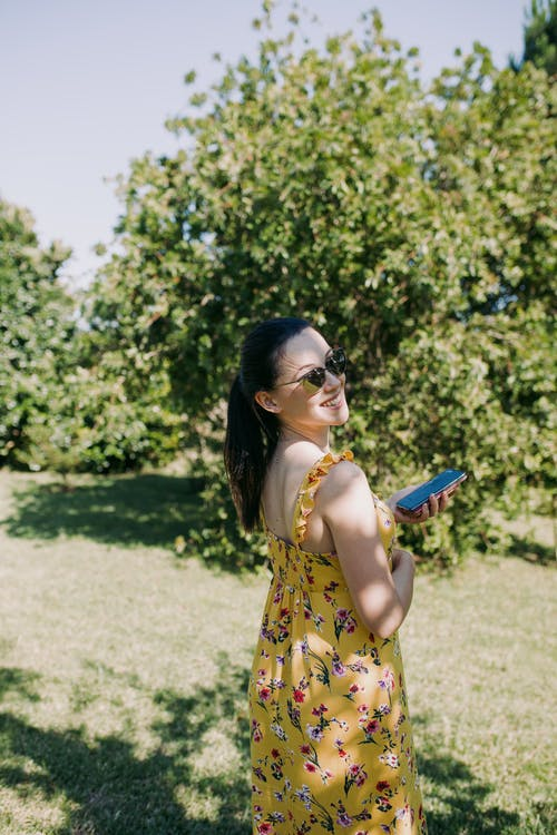 Woman in Yellow and Red Floral Dress Holding Blue and Black Smartphone