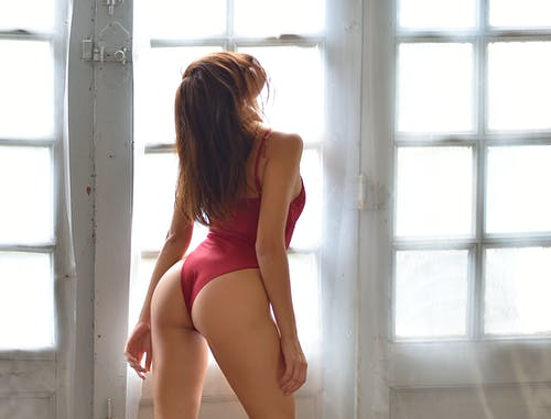 Back view unrecognizable seductive female with flawless body wearing red underwear standing graciously near window in light studio