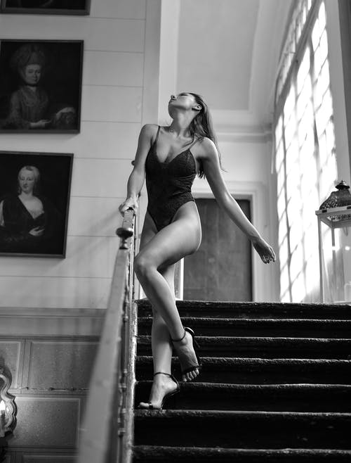 Black and white full body sensual alluring female wearing bodysuit and high heels standing graciously on stairway in light studio