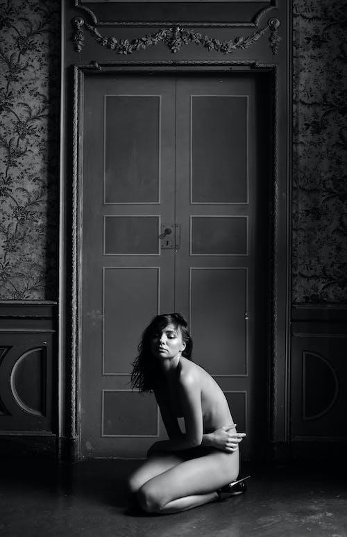 Undressed woman sitting on knees in dark room
