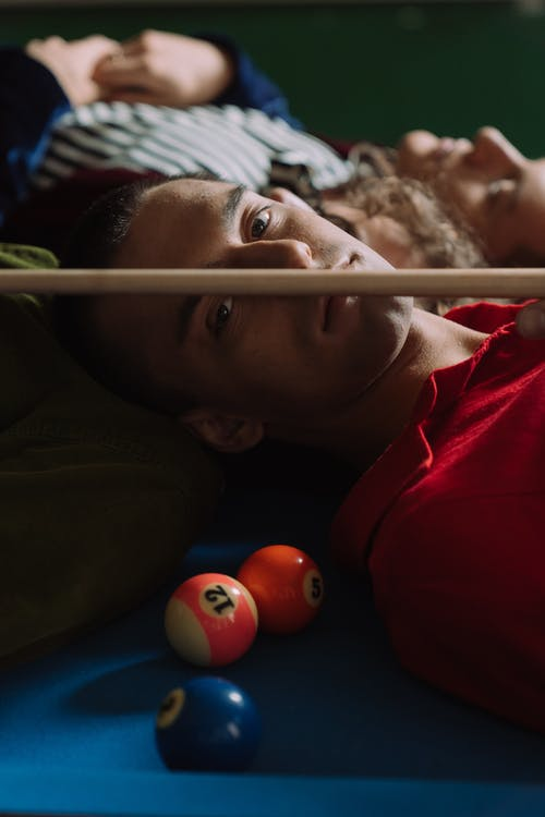 Boy in Red Shirt Lying on Blue and Green Billiard Table