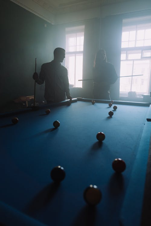 Man in Black and White Striped Long Sleeve Shirt Playing Billiard