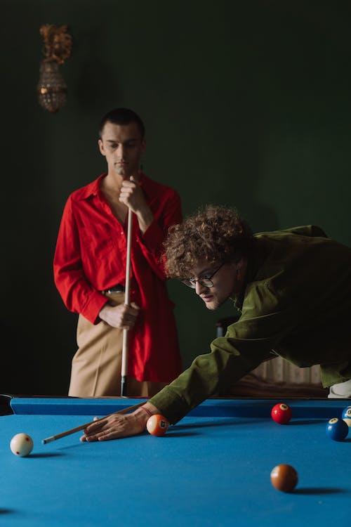 Man in Red Coat Holding Billiard Stick