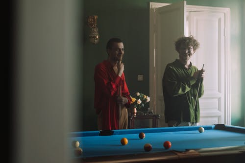 Man and Woman Standing Beside Billiard Table