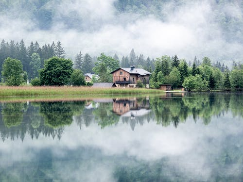 Brown Wooden House Near Green Grass Field and Lake