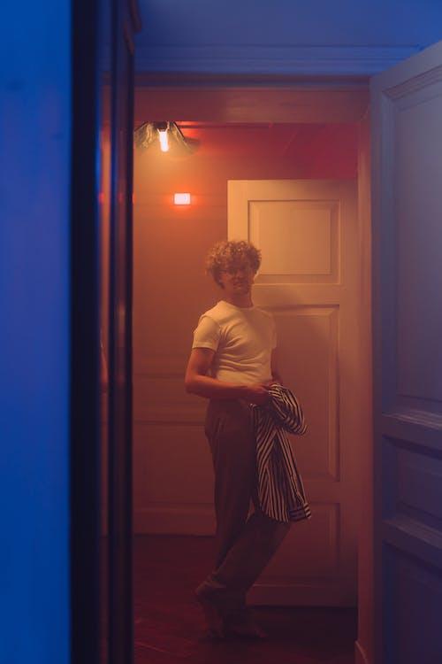 Woman in White Tank Top Standing Near Door