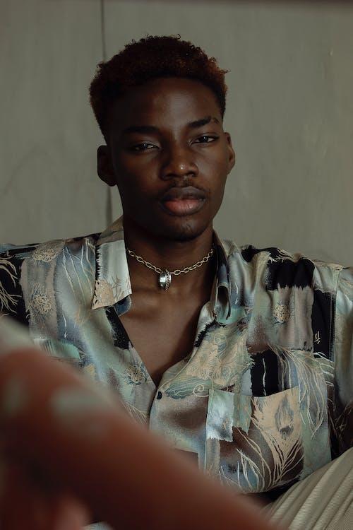 Calm black man in stylish shirt sitting against gray wall