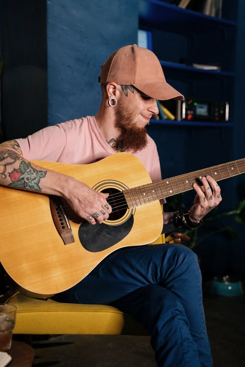 Man With Tattoos Playing an Acoustic Guitar