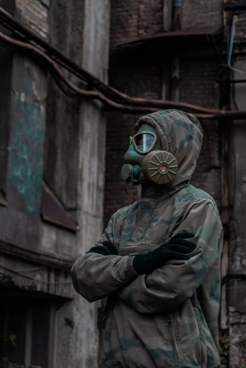 Man in Green and Brown Camouflage Jacket Wearing Gas Mask