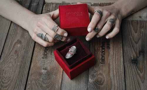 Person Wearing Silver Ring Holding Red Box