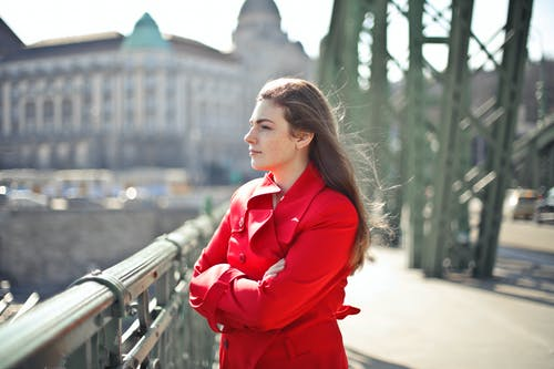 Woman in Red Coat Standing on Bridge