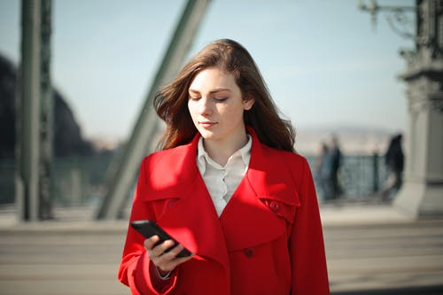 Woman in Red Coat Standing Near Railings