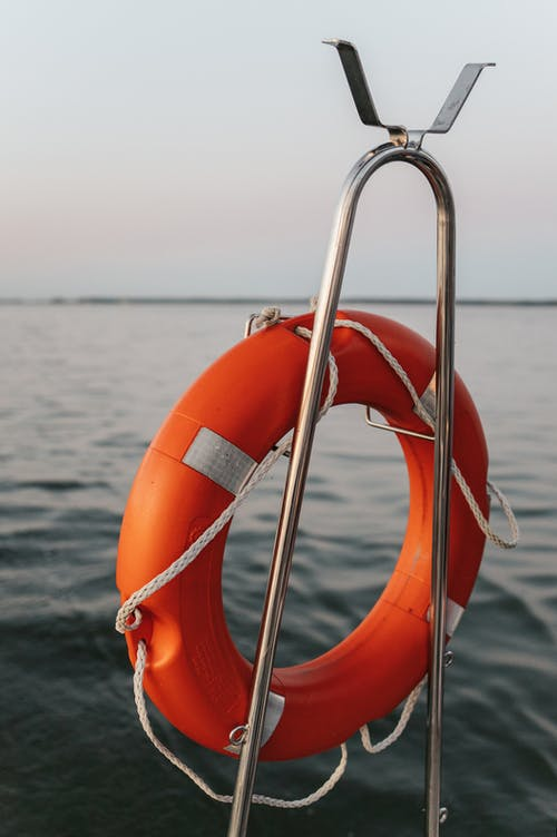 Orange and White Life Buoy on Body of Water