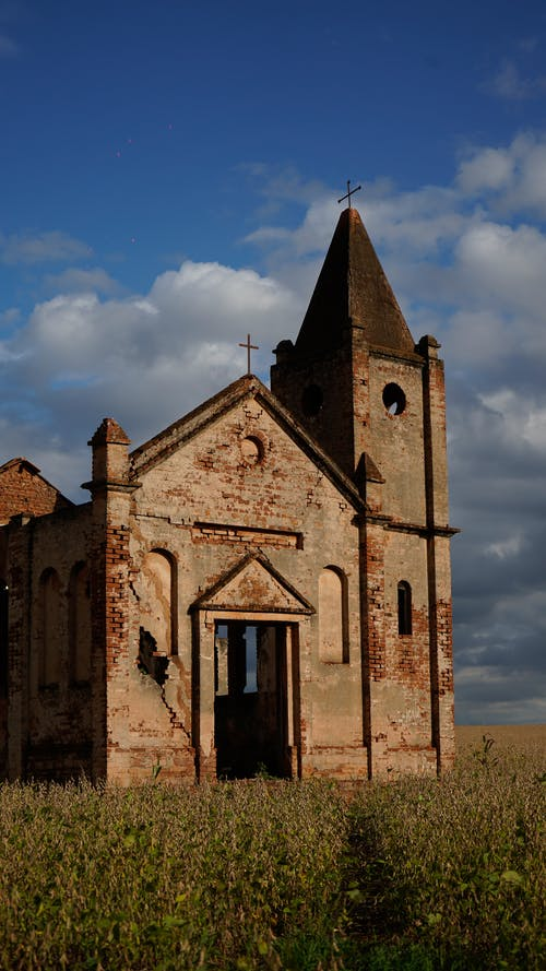 Exterior of destroyed ancient Catholic church with remaining grunge brick walls forgotten on green spacious meadow in countryside