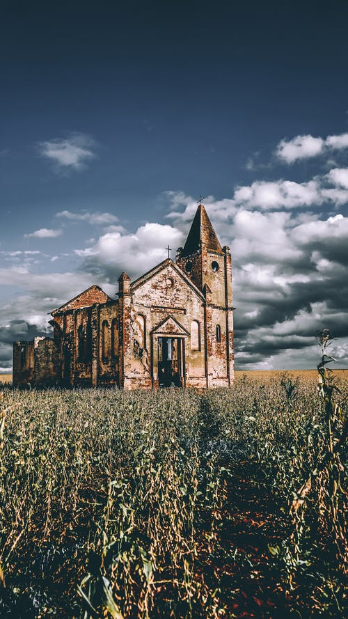 Exterior of ancient desolated masonry church abandoned on grassy vast lawn in remote countryside