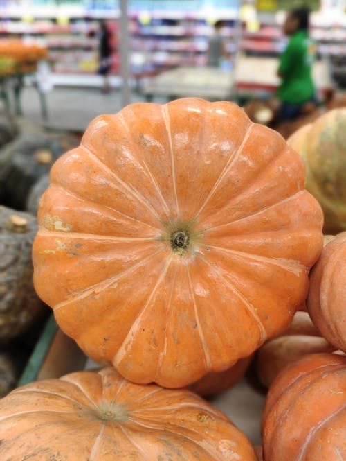 From above of heap of fresh orange pumpkins with ribbed peel for sale in supermarket