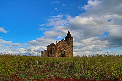 Ground level of abandoned stone church located in green grassy field against cloudy blue sky in Palmital