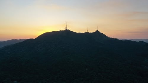 Picturesque scenery of silhouette of Pico do Jaragua mountain with TV towers located in Sao Paulo against sunset sky
