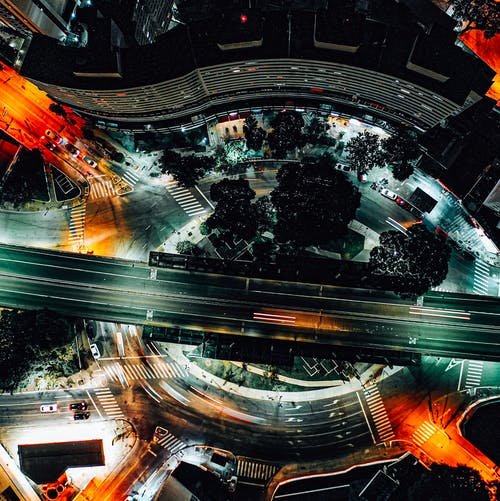 Amazing aerial view of roundabout intersection and straight road with riding cars in modern city district at night