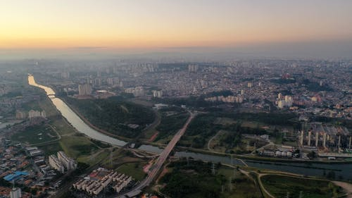 Aerial view of picturesque scenery of long river under bridge and buildings at sundown