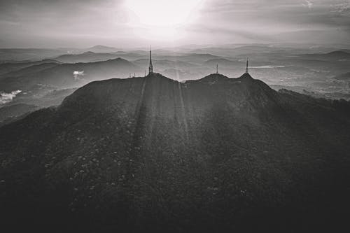 Black and white of mountain range with silhouettes of electric power transmission against hills